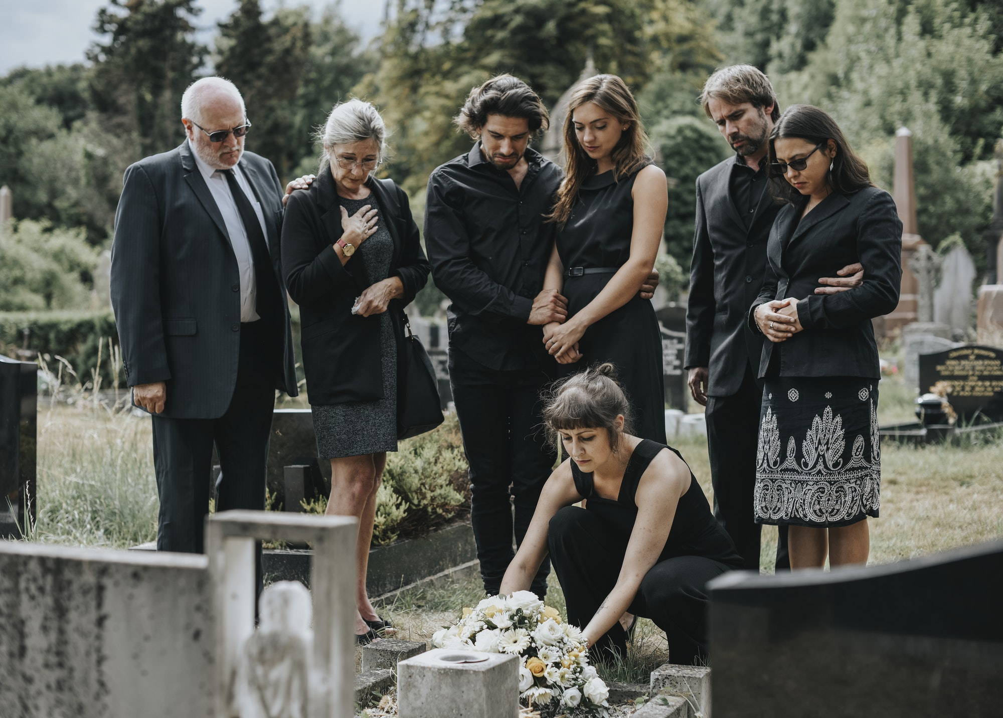 Family laying flowers on the grave